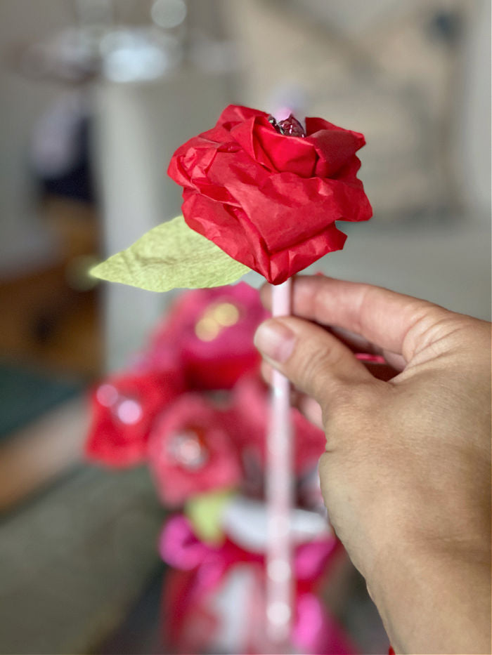 See how to easily make tissue paper rose for Valentine's Day. This easy and affordable craft is the perfect teacher, neighbor, classmate and galentine gift to treat this season! #valentine #valetinesday #roses #candy #crafts #tissuepapercrafts