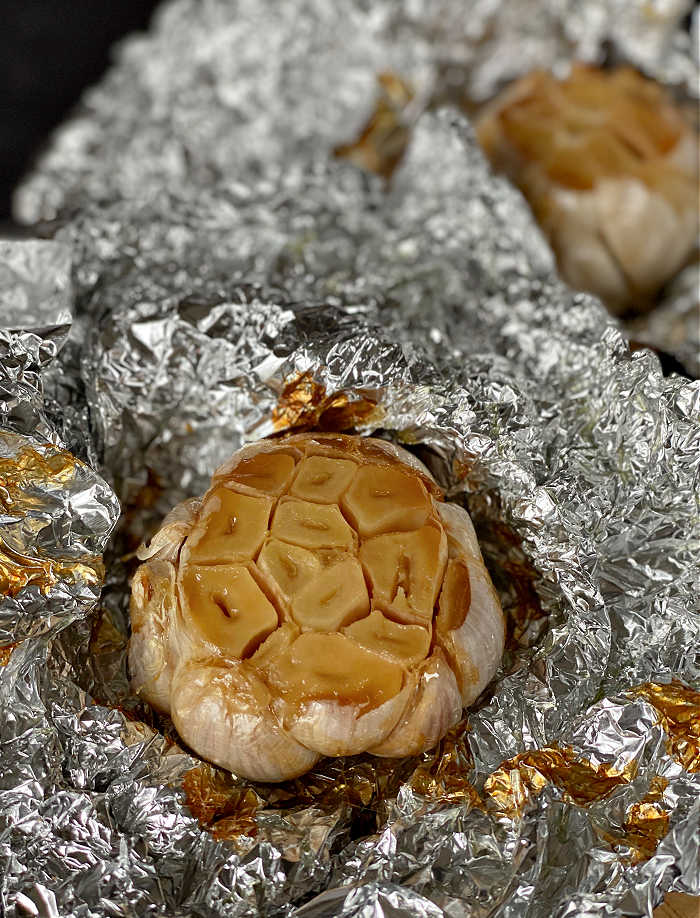 How to roast a garlic bulb in the oven recipe. This easy method delivers creamy and fragrant garlic every time! Serve roasted garlic on its own with crusty bread of mix into any number of delicious recipes. #garlic #roastedgarlic #secretsauce