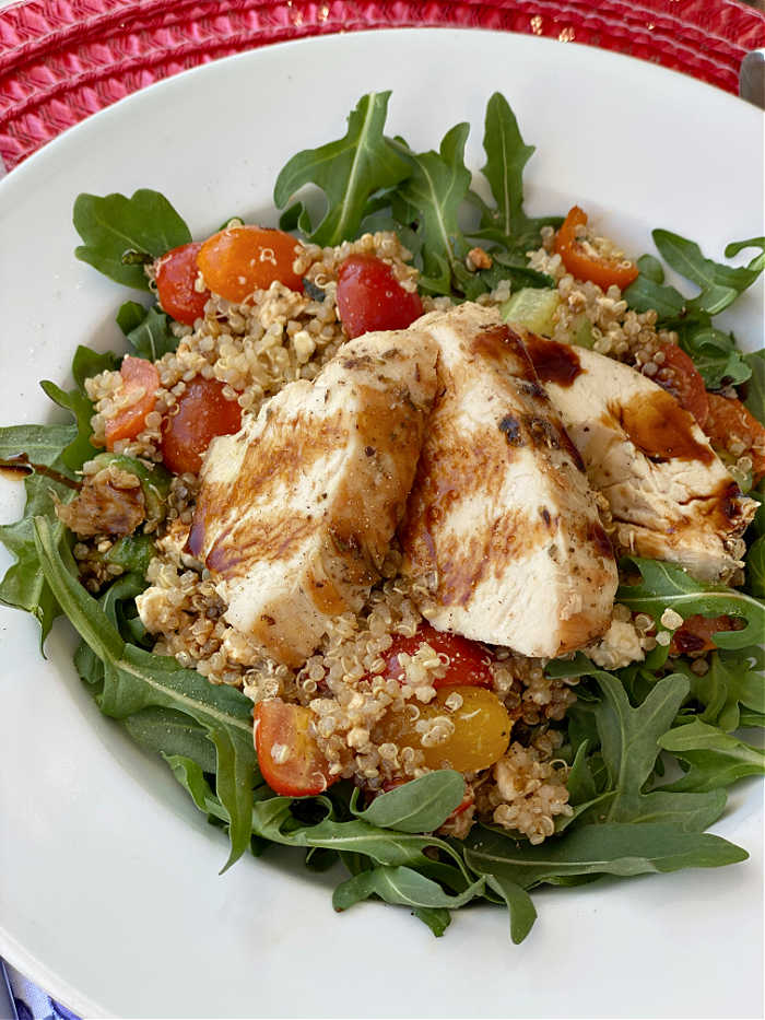 Sliced chicken breast on a bed of quinoa and arugula salad