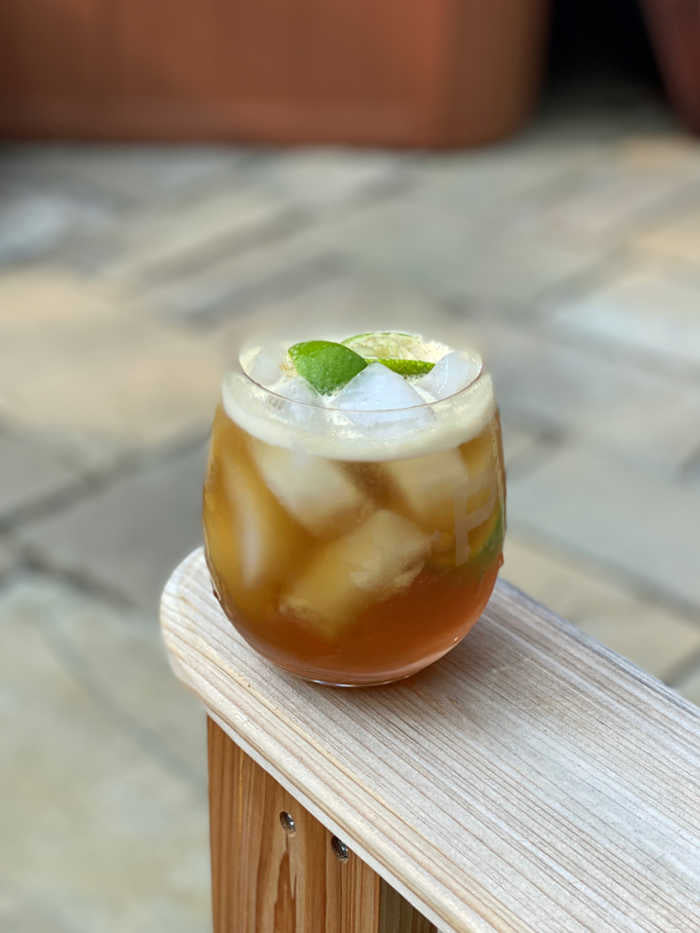Photo of dark and stormy cocktail on an Adirondack chair arm
