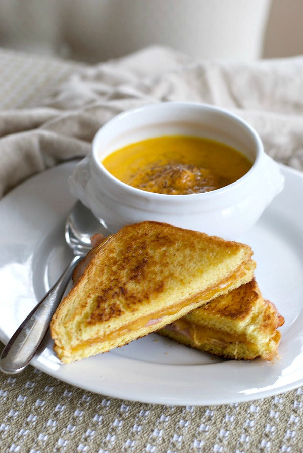 It's a snow day lunch menu for the whole family! Try my creamy carrot and ginger soup with grilled ham and cheese sandwich on thick Texas toast bread. #snowday #kidsfood #lunchideas #soupandsandwich #recipes #lunchrecipes #satsumadesigns