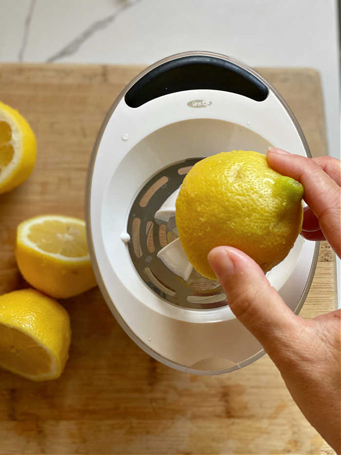 Photo of a lemon being juiced in a small container