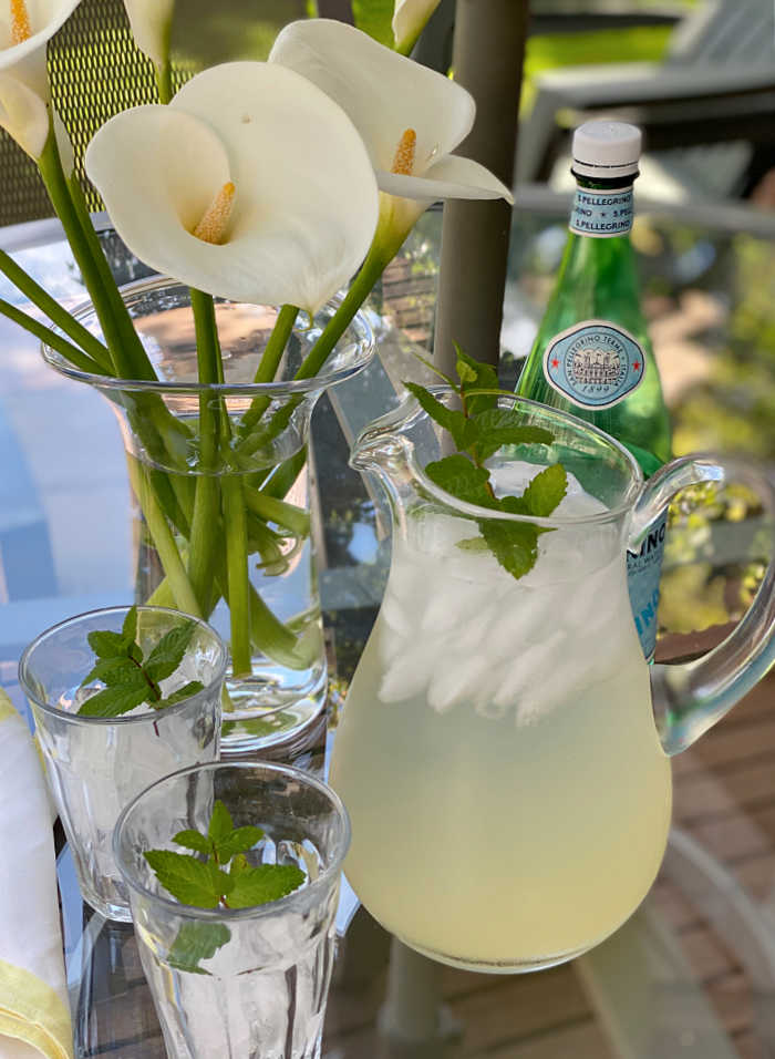 photo of lemonade in a pitcher with calla lilies in a vase and ice in glasses with mint garnish