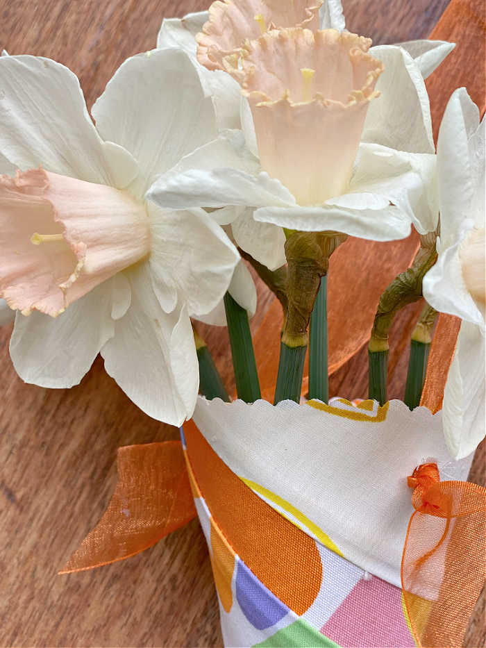 Close up photo of flowers hanging in a paper and fabric cone