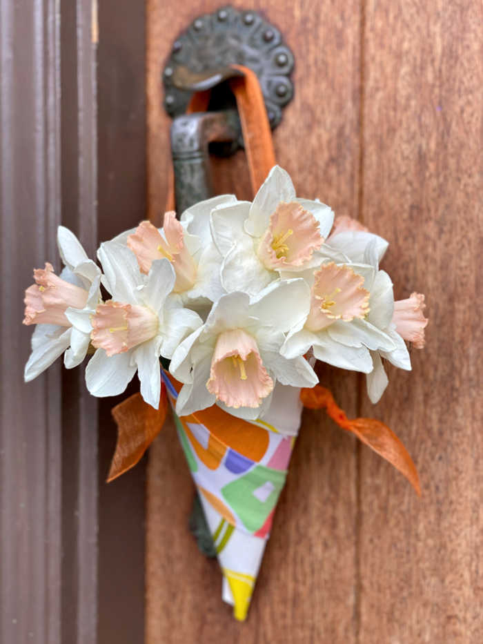 Paper cone filled with flowers on doorknob