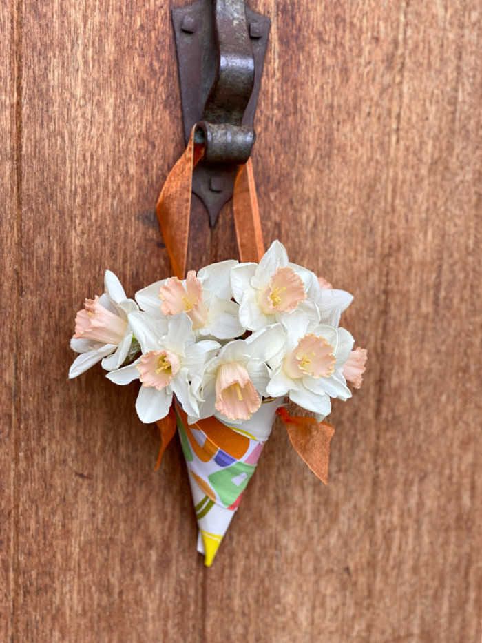 Flowers in a fabric cone hanging from a front door knocker of house