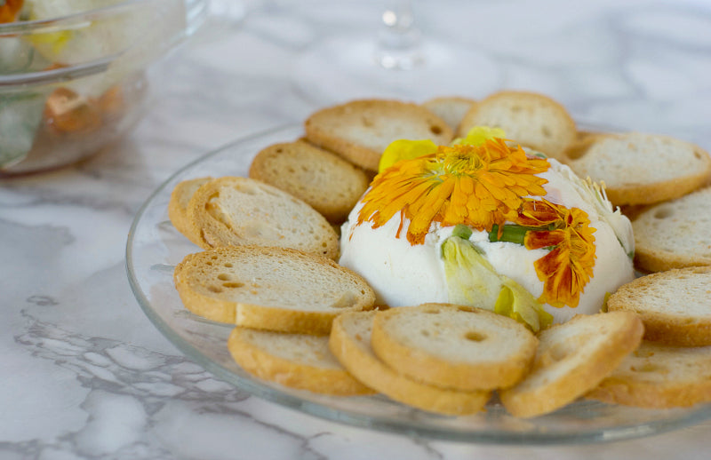 Click through to try my easy flowering goat cheese and crackers appetizer | This pretty appetizer will wow guests and friends when you offer them edible flowers with savory goat cheese and crispy crostini | SatsumaDesigns.com #recipes #edibleflowers