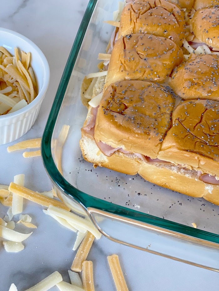 Ham and cheese sliders on Hawaiian rolls with honey mustard dipping sauce. This easy recipe makes great game day food and busy weekday lunch fare. I make these once per week during #distancelearning #covid19 #easyrecipes #lunch #20minuterecipe #sliders #football #potluck #partyfood