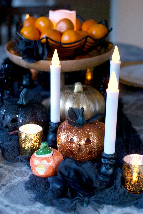 Orange black and gold Halloween tablescape for holiday feasts. Try this easy to assemble tablescape for Halloween parties or to enjoy throughout the season | #halloween #satsumadesigns #partyplanning #dollarstore #layereddesign