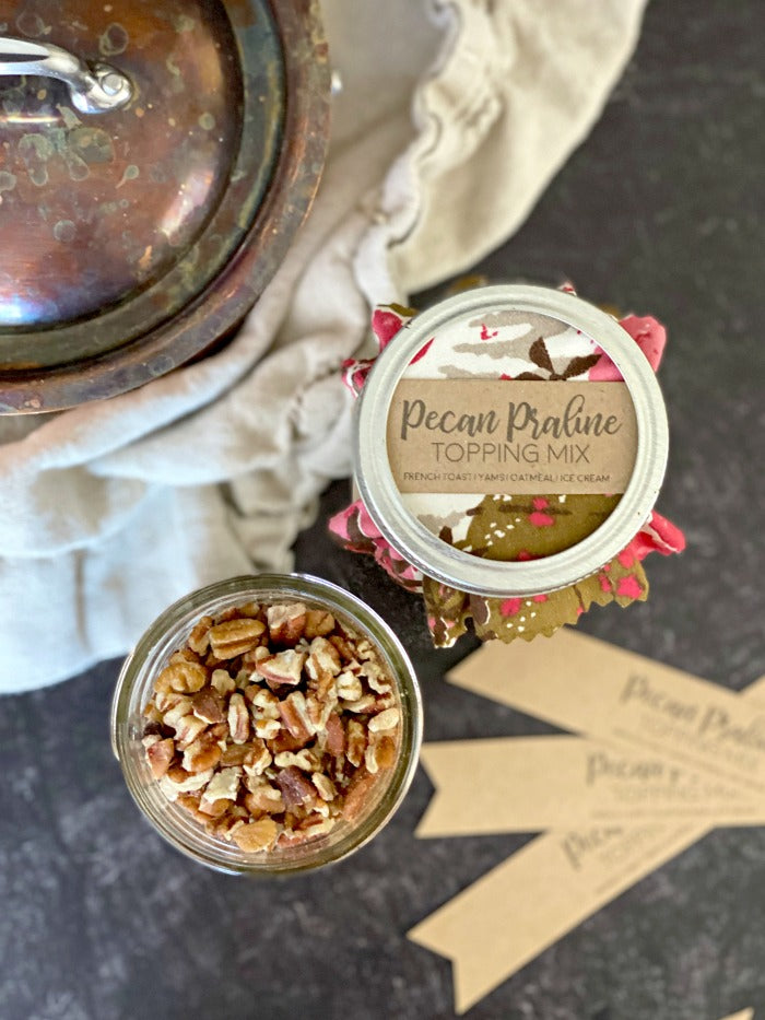 Pecan praline topping mix recipe and gift tag printable are all you need for a perfect holiday hostess gift or little treat for friends, family and neighbors. Just a few ingredients are required for this mason jar gift that can be paired with breakfast or dinner recipes. #masonjarrecipe #masonjargift #printable #hostessgift #holidaygift #praline #thanksgiving #holiday #holidayrecipe
