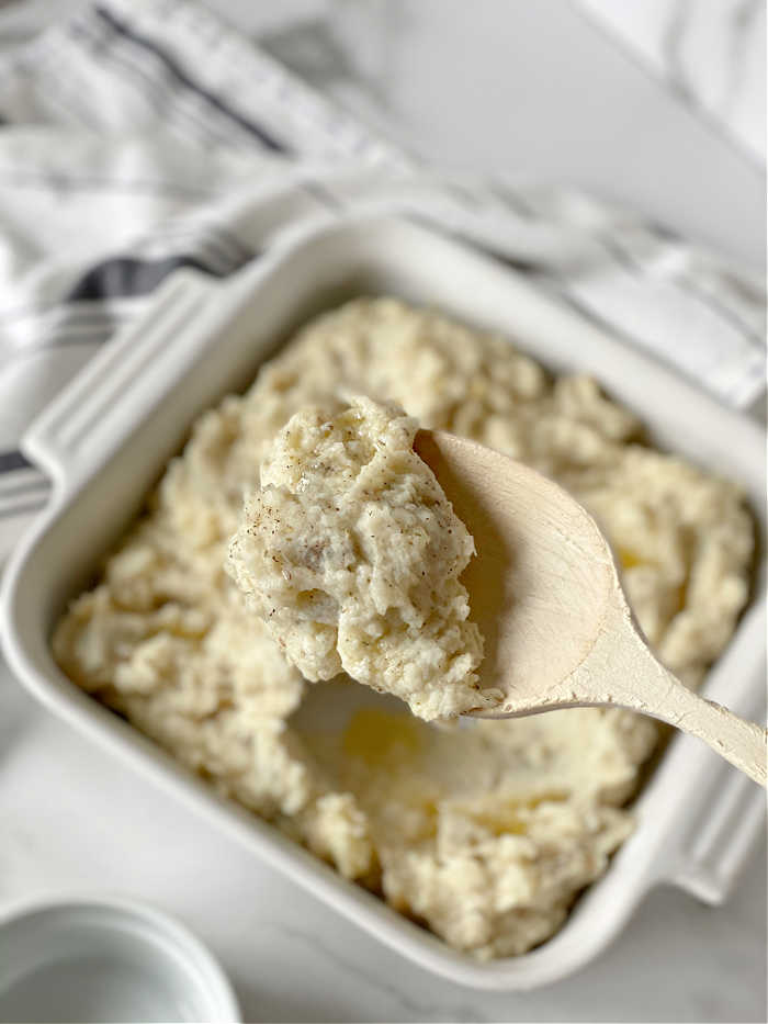 Roasted garlic and herbed cheese mashed potatoes recipe. Try this rich and savory recipe to pair with all your favorite proteins. This recipe makes a love treat! #mashedpotatoes #herbedcheese #roastedgarlicrecipes #thanksgiving