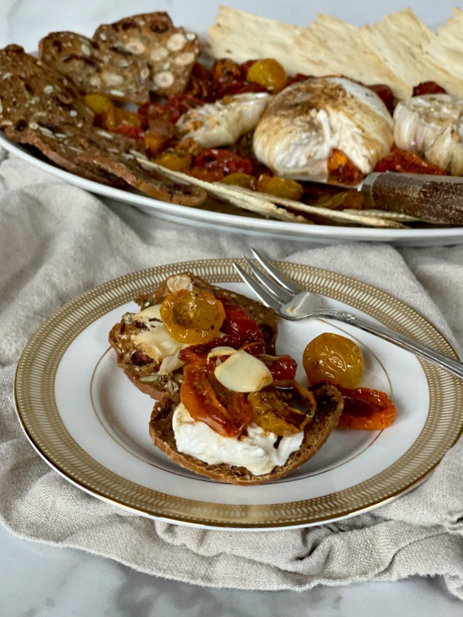 Easy roasted tomatoes and garlic with burrata cheese recipe. Serve this at parties in every season or treat yourself and family to a savory and sweet treat for snack or evening meal. #bonappetit #burrata #mezzeplatter #appetizers #appsrecipes #easyappetizers #roastedtomatoes #tomatoes #garlic #cheese