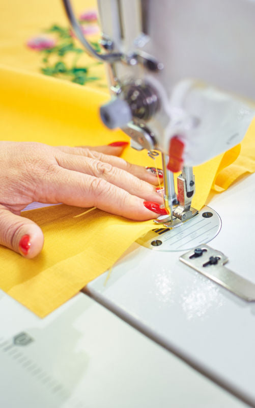 Photo of hand sewing yellow fabric