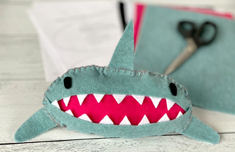 Sew easy shark tooth fairy pillow is the perfect project for little hands. Try this tooth fairy pillow with kids who are learning to sew. Or bypass needle and thread and simply use a glue gun to complete! #toothfairy #kids #sewing #beginnersewing #embroidery #blanketstitch #craft #crafty #crafts #feltcrafts