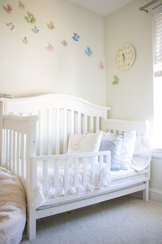 4-in-1-crib in a nursery with butterflies on the wall