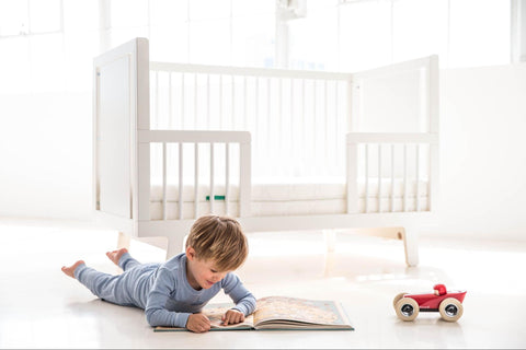 Young kid reading on the floor near his 4-in-1-crib
