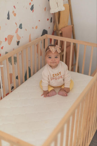 baby sitting up in 4-in-1-crib