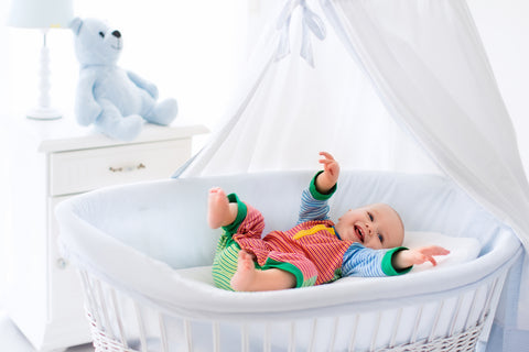 happy baby in a portable bassinet