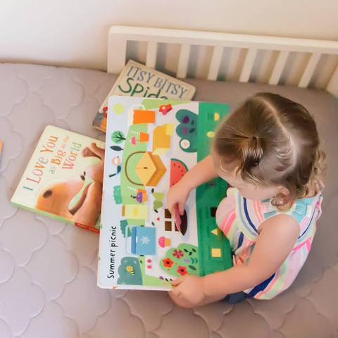 toddler looking at books in a crib