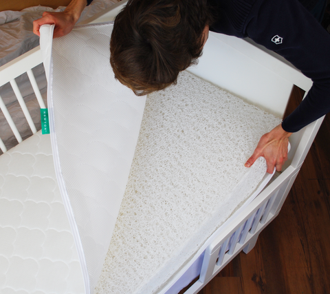 man taking the cover off a Newton Baby crib mattress