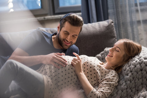 Expecting parents lounging on a sofa and creating a birth plan