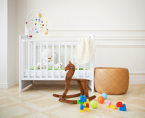 White mini crib in a nursery