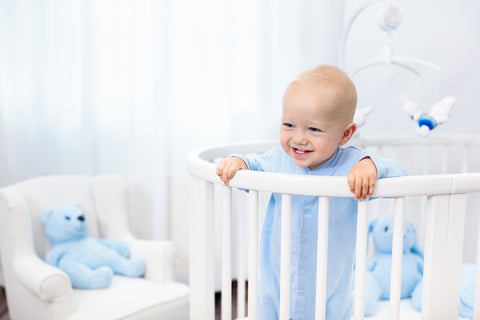 Baby standing up in his white shaped crib