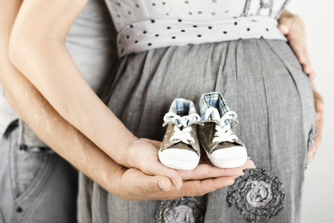 Expecting mom and dad holding baby shoes