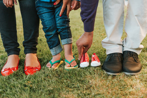 Gender reveal idea photo of mom, dad, and baby's shoes