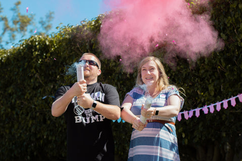 Expecting mom and dad exploding colors for a gender reveal