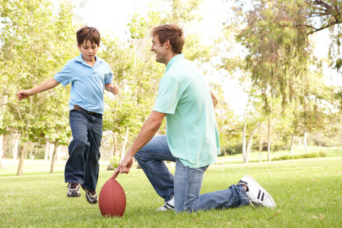 Father teaching his son how to kick a football