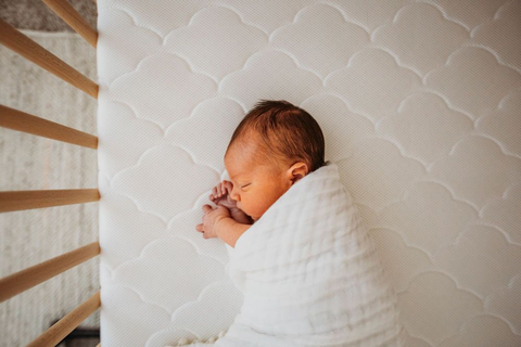 baby sleeping on a Newton Baby crib mattress