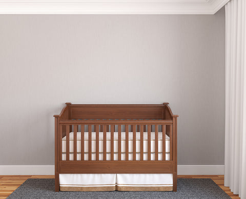 baby bed with crib sheets in an empty nursery