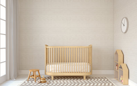 wood-colored baby bed with crib sheet in a neutral nursery
