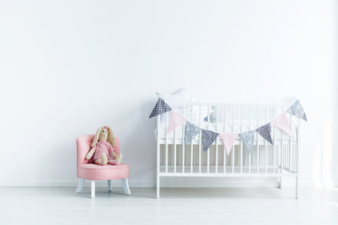 baby nursery with white crib and pink chair