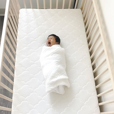 Minimalist baby wrapped in a Newton swaddle in a crib