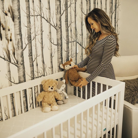 Mom-to-be looking at stuffed bears in her baby's nursery