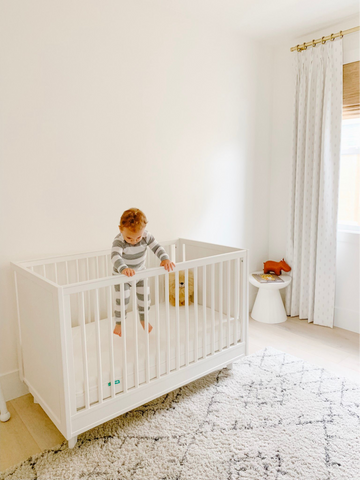 Baby standing in white crib