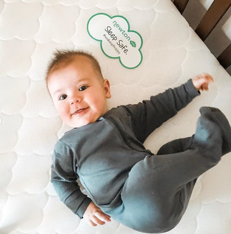 Smiling baby on a Newton Baby crib mattress