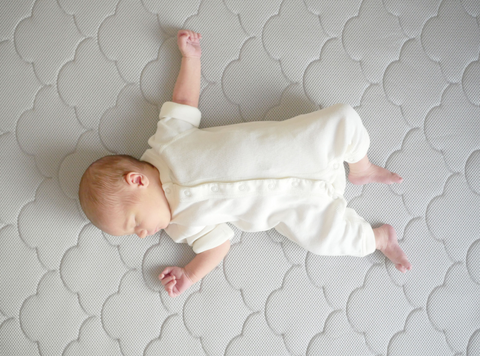 baby sleeping on a gray crib mattress