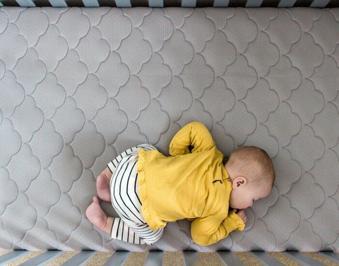 Baby sleeping on his stomach on an organic mattress