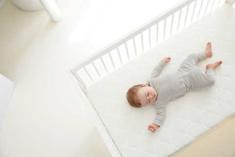 Baby sleeping in a white crib