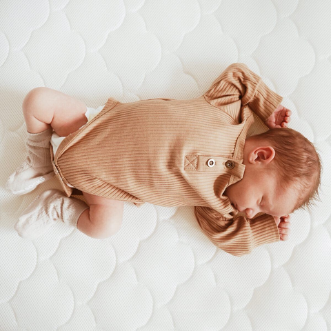 Newborn sleeping on a Newton Baby Mattress