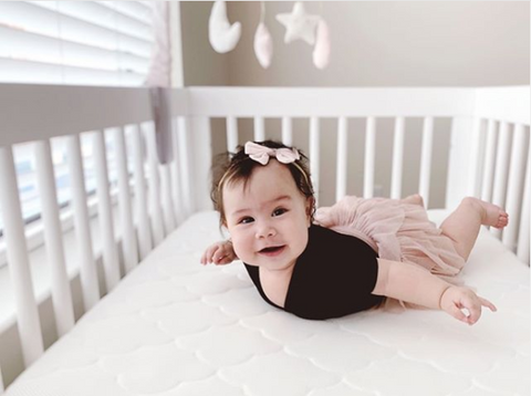 Baby rolling over on her tummy in a crib