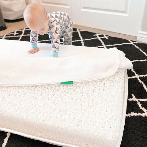 baby on crib mattress that has a cover coming off