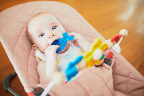baby chewing on teether in baby bouncer