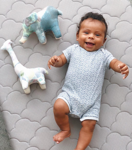 baby boy playing with stuffed animals on a newton baby crib mattress