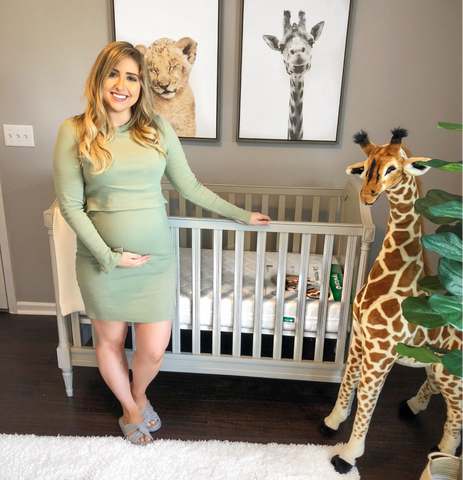 pregnant woman standing in front of a crib in a safari themed baby boy nursery