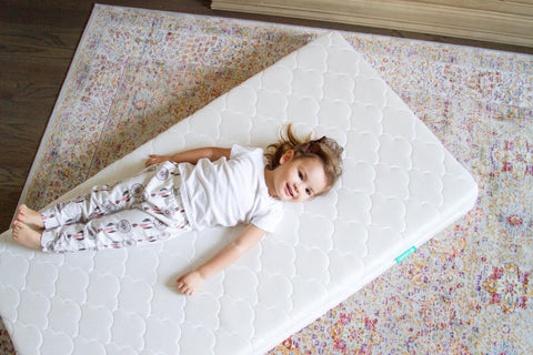 toddler laying on crib mattress