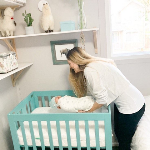 baby cries in sleep while mom lays her down in crib